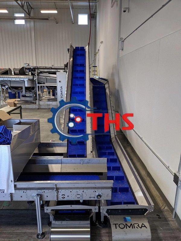 Băng tải nhựa được gắn thêm cánh gạt đưa hàng lên dốc
